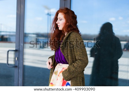 Portrait of a beautiful redhead woman in the shopping mall - stock photo