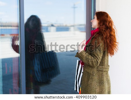 Portrait of a beautiful redhead woman in the shopping mall blue mirror background, corrects hairstyle, shopping bag in black and white line - stock photo