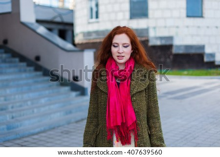 Portrait of a beautiful redhead woman is dreaming near the stairs and smiling, eyes closed, green coat, pink scarf outdoor, spring - stock photo