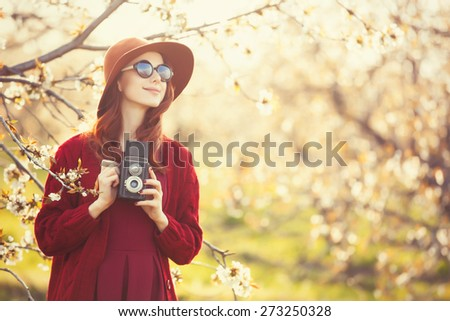 Portrait of a beautiful redhead women in red sweater and hat with camera in blossom apple tree garden in spring time on sunset. - stock photo