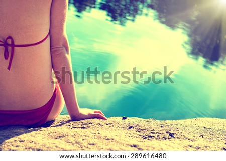 Portrait of a beautiful relaxed woman on the beach with blue water background. Back view, instagram filter. - stock photo