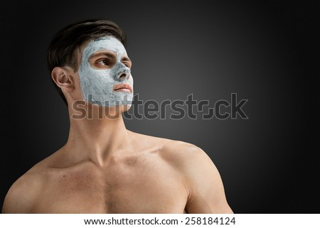 Portrait of a beautiful relaxed young man with a facial mud clay mask, face and body skin care treatment. - stock photo