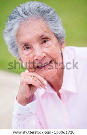 Portrait of a beautiful retired woman smiling outdoors