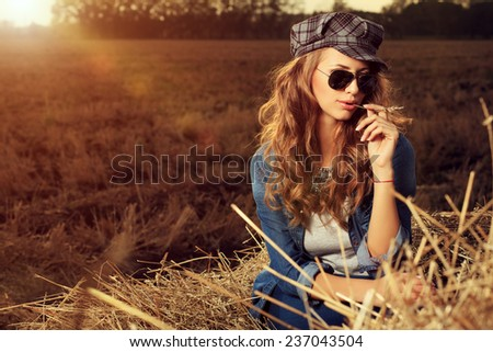 Portrait of a beautiful romantic young woman in the countryside at sunset. - stock photo
