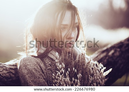 Portrait of a beautiful sad brunette girl outdoors in autumn - stock photo