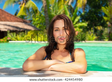 Portrait of a beautiful seductive woman in a pool on the luxury tropical beach resort, with pleasure spending summer holidays on an island