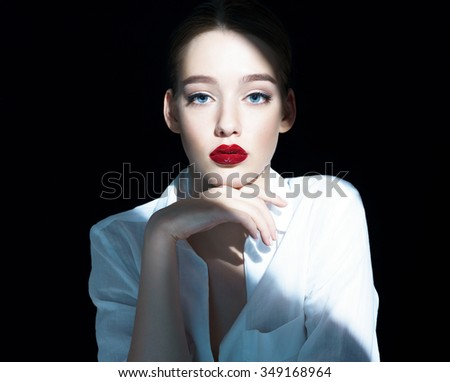 Portrait of a beautiful sensual brunette girl with red lips / close-up of an attractive girl of the European appearance in a white shirt, photography on a dark background. - stock photo