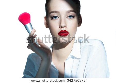 Portrait of a beautiful sensual brunette girl with tassel, skin care concept / photoset of attractive girl holding a make-up brush on white background - stock photo