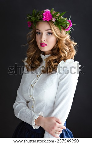 Portrait of a beautiful sensual girl in a white elegant blouse with a wreath of flowers on his head, on a dark background in Studio - stock photo