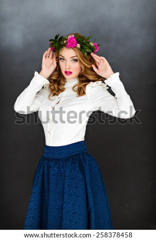 Portrait of a beautiful sensual glamorous yellow-haired girl in a white blouse and a blue skirt with a wreath of flowers on his head, in the Studio on a dark background - stock photo