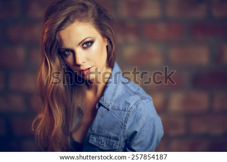 Portrait of a beautiful sensual sexy girl with long blond hair in a denim shirt over a dark brick background in Studio