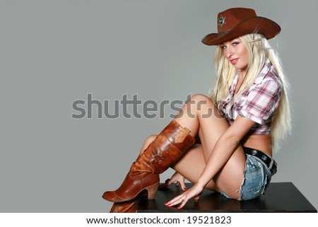 Portrait of a beautiful sexy rodeo girl on gray background - stock photo