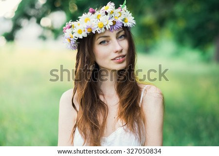 portrait of a beautiful sexy smiling girl with a wreath on his head in the spring park - stock photo