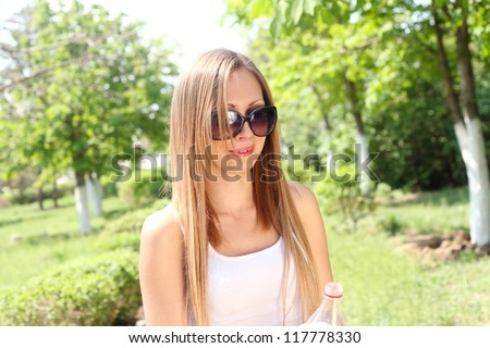 Portrait of a beautiful sexy woman outdoors playing with water in bottle having fun - stock photo