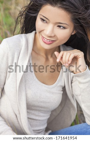 Portrait of a beautiful sexy young Chinese Asian woman or girl relaxing outside - stock photo