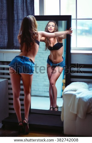 Portrait of a beautiful sexy young woman looking into mirror