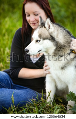 Portrait of a Beautiful Siberian Husky dog outdoors with his woman owner behind him