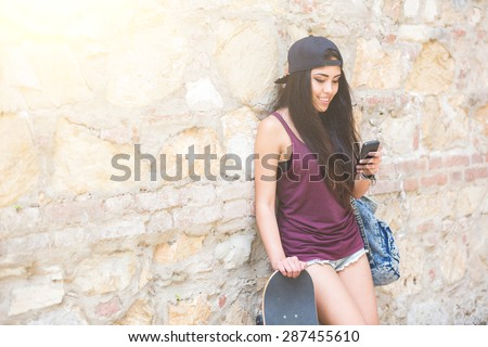 Portrait of a beautiful skater girl looking at smart phone against stone wall. She is half caucasian and half filipina, she wears short jeans, a purple tank top and a black cap. - stock photo