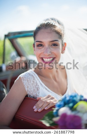 Portrait of a beautiful smiling bride holding her bouquet in a convertible retro car.  Focus on the face - stock photo