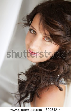 Portrait of a beautiful smiling bride with wedding hairstyle.