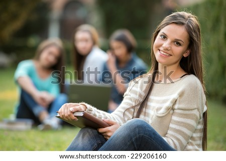 Portrait of a beautiful, smiling college girl is holding book with blurred students are sitting in the park. She is looking at the camera. - stock photo
