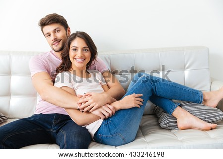Portrait of a beautiful smiling couple sitting on the sofa isolated on white background - stock photo