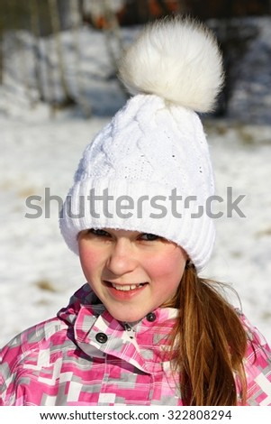 Portrait of a beautiful smiling girl in a white winter cap - stock photo