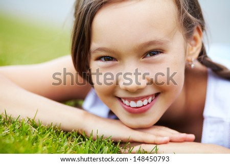 portrait of a beautiful smiling girl lying on the grass in the park