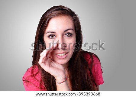 Portrait of a beautiful smiling student talk to you. Isolated on gray background, caucasian beauty - stock photo