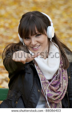 Portrait of a beautiful smiling woman listening to music with thumb up - stock photo