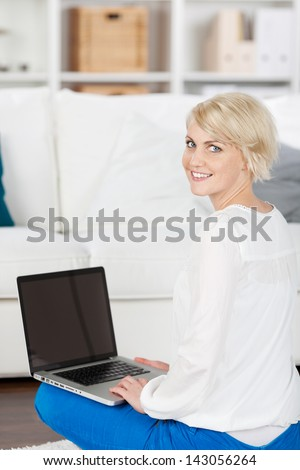 Portrait of a beautiful smiling woman with laptop sitting on floor at home