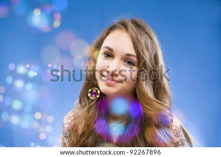 Portrait of a beautiful smiling young brunette girl among colorful soap bubbles. - stock photo