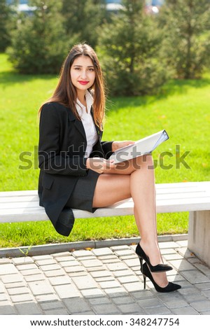 Portrait of a beautiful smiling young business woman sitting on a bench outdoor. Bright green grass as background. - stock photo