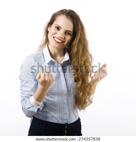 Portrait of a beautiful smiling young woman dressed in a blue shirt on a white background in victory gesture - stock photo