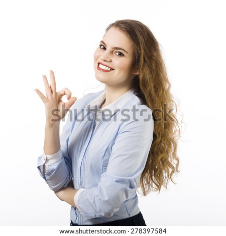 Portrait of a beautiful smiling young woman dressed in a blue shirt on a white background in gesture of satisfaction - stock photo