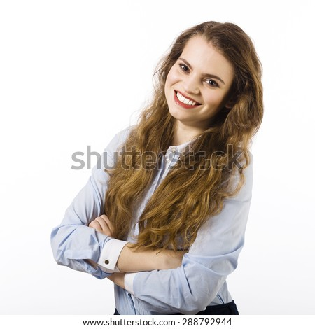 Portrait of a beautiful smiling young woman dressed in a blue shirt on a white background in passive attitude