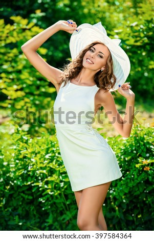 Portrait of a beautiful smiling young woman in light white dress and hat in the summer park. Beauty, fashion. Holidays.  - stock photo