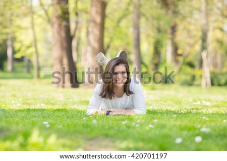 Portrait of a beautiful smiling young woman lying on grass in a park and looking at camera. She is enjoying nice and sunny spring day in nature.