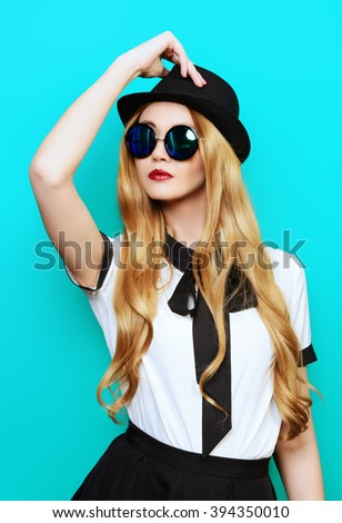 Portrait of a beautiful smiling young woman wearing pretty blouse, hat  and sunglasses. Studio shot over aquamarine background. - stock photo