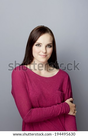 Portrait of a beautiful smiling young woman with long brown hair. Wearing purple top. On gray studio background - stock photo