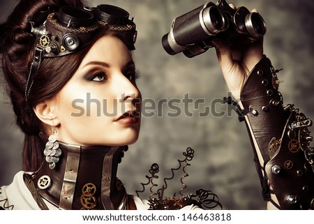 Portrait of a beautiful steampunk woman looking through the binoculars over grunge background. - stock photo