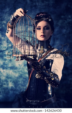 Portrait of a beautiful steampunk woman with a cage over grunge background. - stock photo