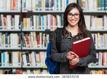 Portrait of a beautiful student in a library - stock photo