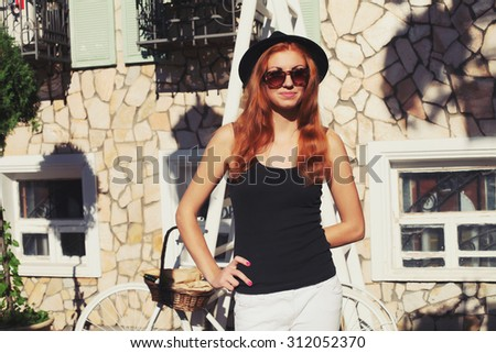 portrait of a beautiful stylish hipster woman in a hat with a bicycle on city background in the sunlight outdoor