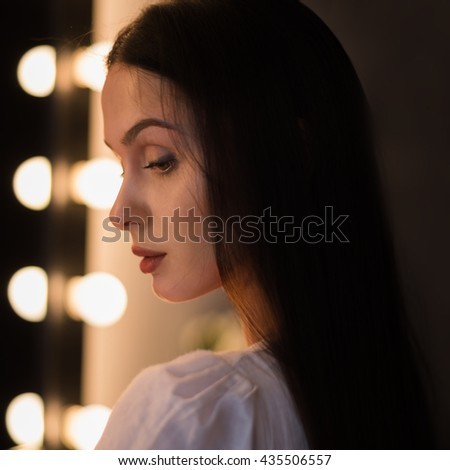 portrait of a beautiful stylish young girl model on the background of the mirror make-up artist and studio