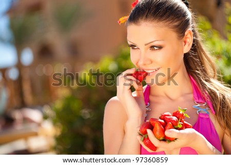 portrait of a beautiful Summer Woman on vacation with strawberry in her hands - stock photo