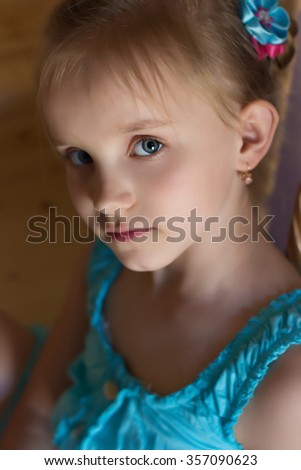 portrait of a beautiful sweet little girl in a blue dress with blue eyes