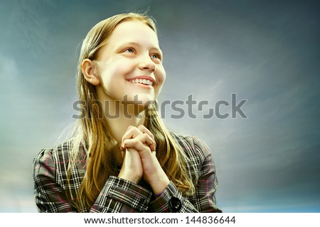 Portrait of a beautiful teen girl smiling on a sky background - stock photo
