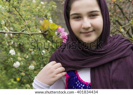 Portrait of a Beautiful Teenage Girl Outdoor in A Garden Viewing Directly to the Camera  - stock photo