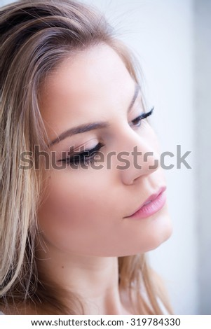 Portrait of a beautiful teenage girl with window in the background - stock photo